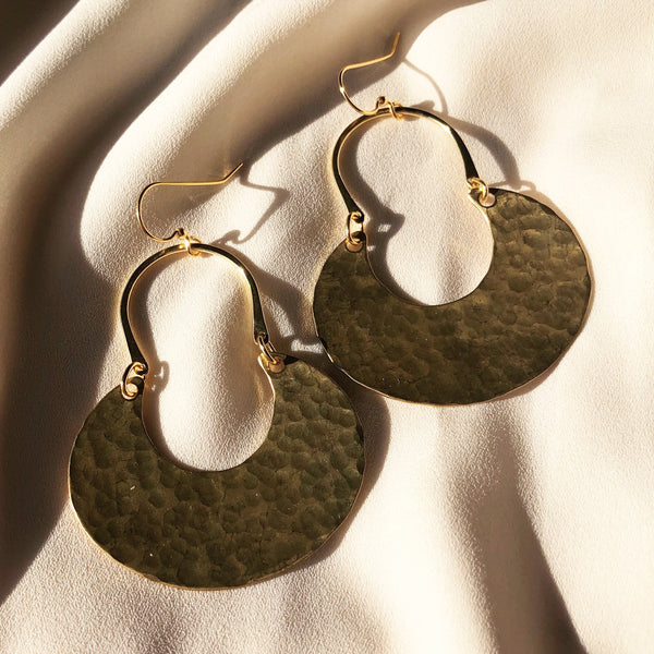 gold moon earrings, handmade and resting in the sunlight
