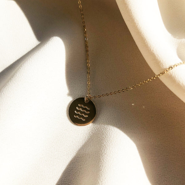 gold disc necklace hand stamped with  ocean waves, laying in the sunlight
