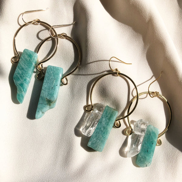amazonite stone and quartz crystal gold earrings laying in the sunlight
