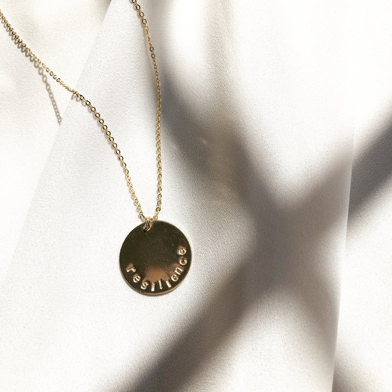 custom gold disc necklace, this one says resilence on the gold disc necklace