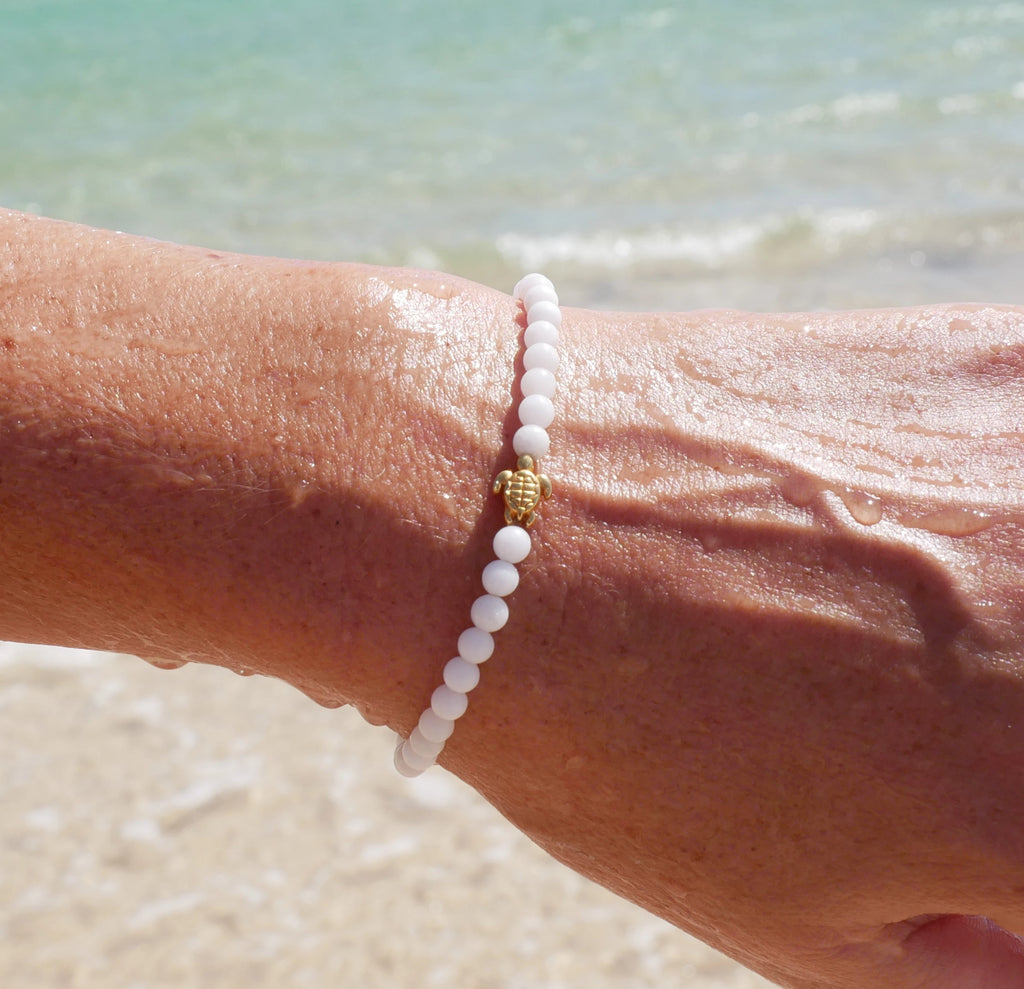 Beach picture of snowy / white turtle bracelet with gold turtle