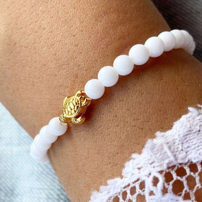 Close up picture of snowy / white turtle bracelet with gold