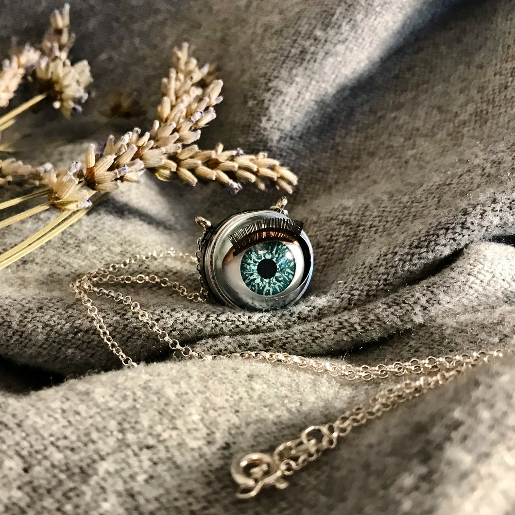 aqua coloured doll eye with metal casing hung on sterling silver chain, item displayed on soft grey fabric with  dried lavender