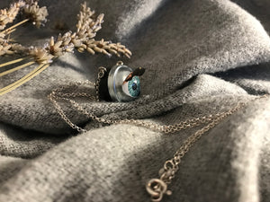 Side view of aqua doll eye necklace displaying the lashes that will flutter when the doll eye blinks