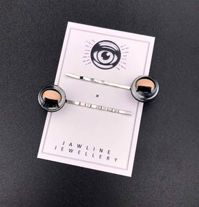 Doll eye hairgrips shown with packaging, on black and white Jawline jewellery card with logo.  item is laying down, so the eyes are closed