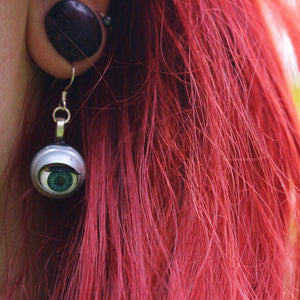 close up of blinking doll eye earring being worn by model with red hair and stretched ear lobes