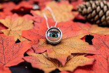 Load image into Gallery viewer, Eyeball partially open showing the blue and green colour and long lashes, sat on autumnal leaves