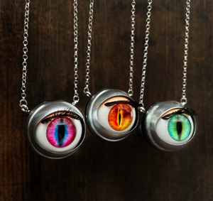 fantasy style doll eye necklaces with reptilian/ feline eyes shown in pink, fire and green
