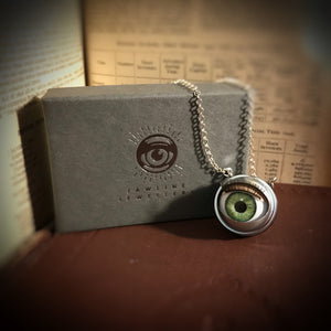 green doll eye necklace shown with jewellery box - box is grey with silver foil eye logo