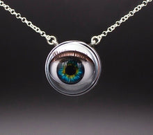 Load image into Gallery viewer, Blinking doll eye necklace with bright green and blue iris on sterling silver chain with grey beckground