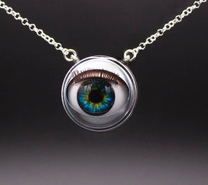 Blinking doll eye necklace with bright green and blue iris on sterling silver chain with grey beckground