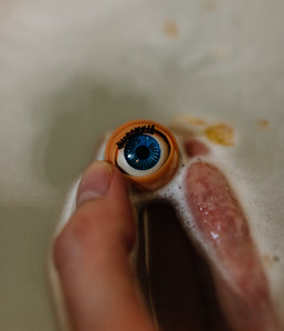 Blinking doll eye shown held in bath water as the eye has been released from the bath bomb