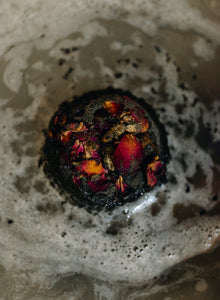 Black bath bomb shown fizzing in the water releasing dried rose petals and turning the bath water grey