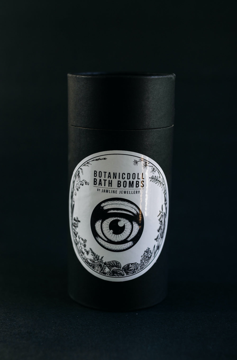Jawline JewellerY Botanicdoll Bath bomb gift packaging - Black cardboard tube with white round label showing doll eye logo with plants, shown on black background