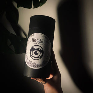 dark image with hand showing bath bomb packaging, there are dark shadows from the product and plant leaves