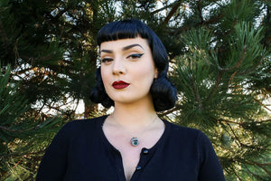 Pin up woman with dark eyemakeup wearing the northern lights eyeball necklace with trees behind