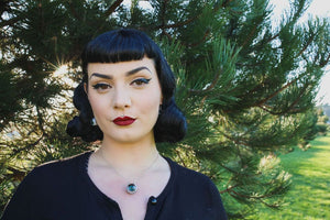 Pin up model in nature wearing eyeball necklace with green blue iris