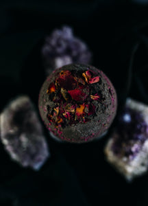 Black back bomb with dried red rose petals shown on black background with amethyst crystals in the background