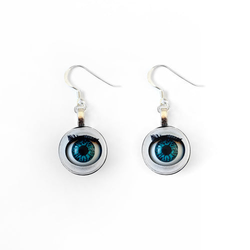 Blinking doll eye earrings shown on plain white background, earrings are made with vintage style doll eyes with blue irises.