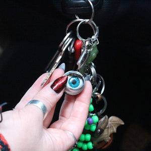 doll eye keychain with blue eye and long lashes, held by someone with long red glitter nails