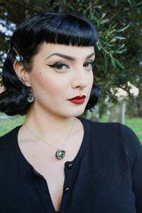 pin up model with classic makeup wears matching green doll eye necklace and earrings