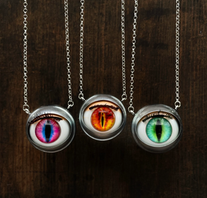 Doll eye necklaces with fantasy style, showing pink cat eye, red and yellow dragon eye and green feline eye with dark wooden background