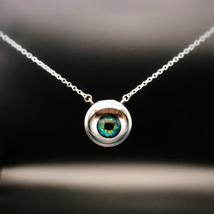Silver necklace with doll eye pendant and green and blue iris, with long eye lashes
