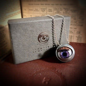 Purple doll eye necklace shown with grey packaging and silver foil design