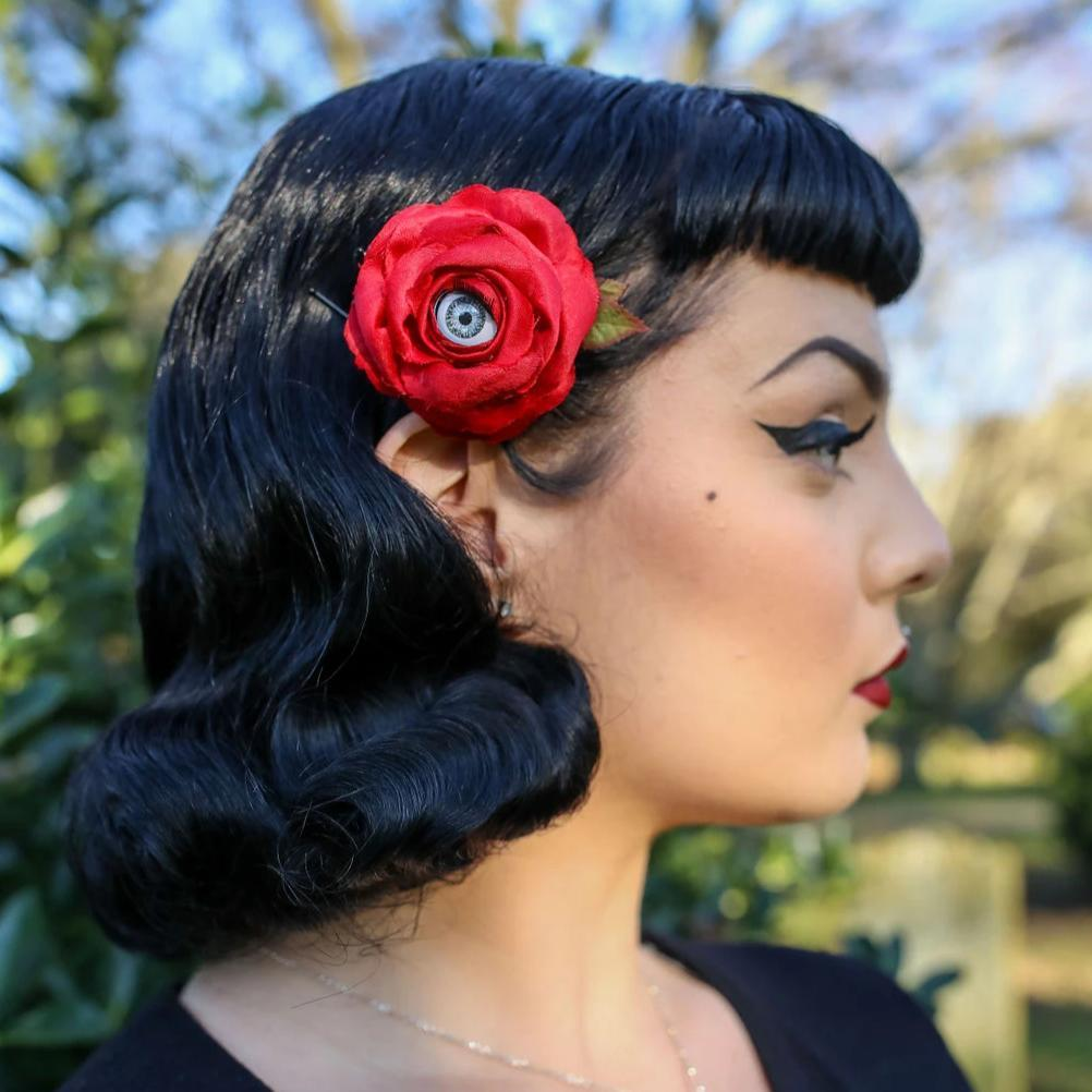 Large red rose with grey eye hair accessory worn by model with pin up/ rockabilly style