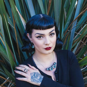 Large necklace made from doll eyes being worn by pin up/gothic model infront of large plant