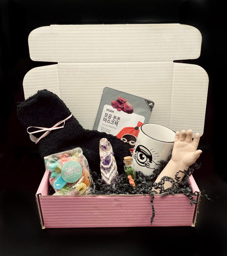 gothic self care package, a light pink box showing contents of black fluffy socks, vegan sweets, an amethyst crystal, a mug, a doll part, face mask and small glass vial with minature doll inside.