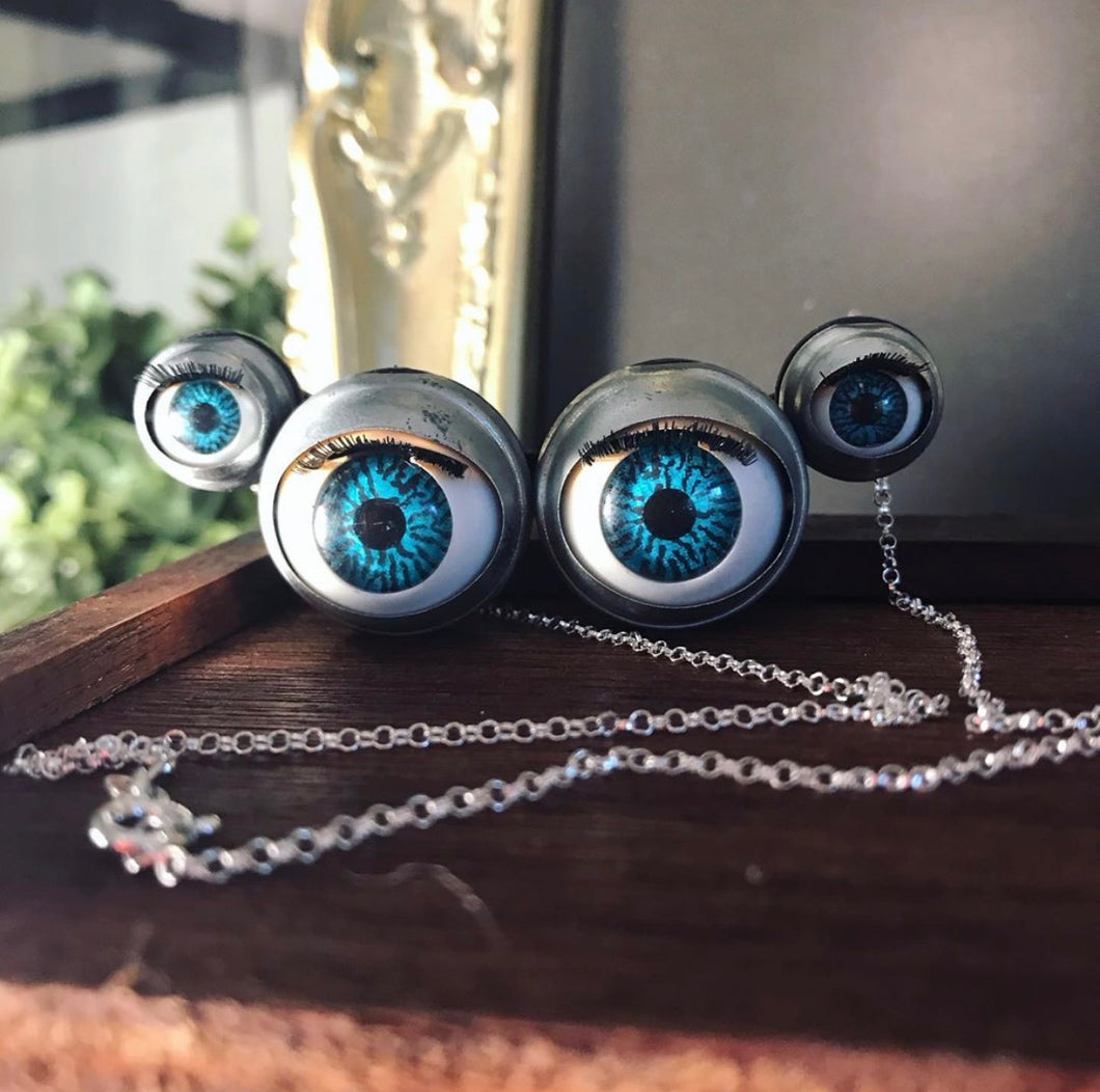 Large necklace made from 4 blinking doll eyes attatched together to form the shape of spider eyes, displayed on wooden background