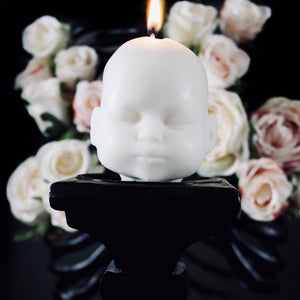 White doll head candle on black pilar with white rosese in the background, dark gothic image