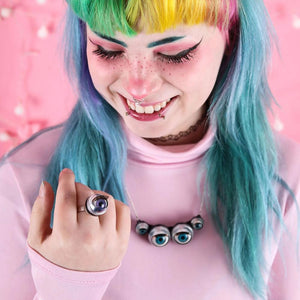 model with rainbow hear and bright pink clothing looks at purple ring, also wearing spider necklace