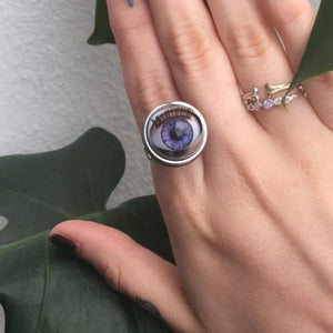 close up of doll eye ring shown on hand with other rings and foliage in background