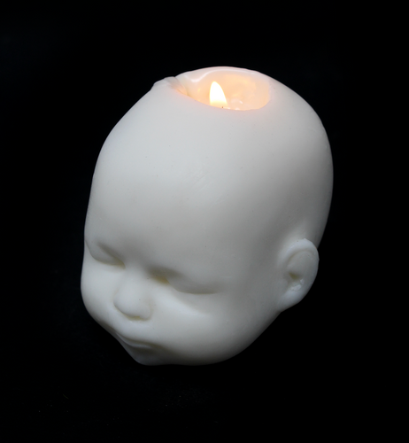 white doll head shaped candle shown burning with flame on black background