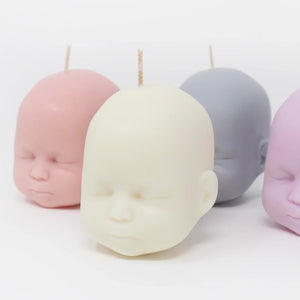 group shot showing different colours available of doll hed candles, white, peach, grey and purple on white background