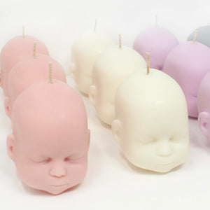 group image showing different colours of doll head candles available, pink, white, purple grey