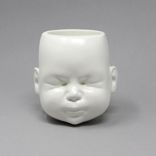 White pot in the shape of a doll head on grey background