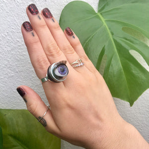 purple doll eye ring won on finger showing hand with leaves in background