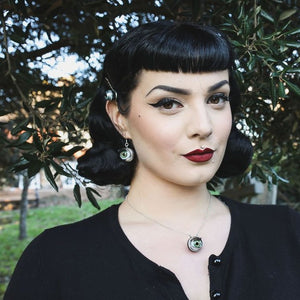 pin up model with black hair and dark eye makeup wears green eyeball necklace and matching earrings in nature with a ewe tree
