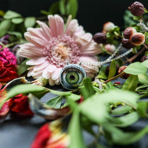 green doll eye shown on drk background with flowers