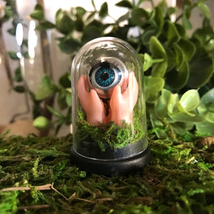 jawline jewellery minature curiosity diorama dome made from blinking doll eye and hands pushing up from the earth, made with real moss.