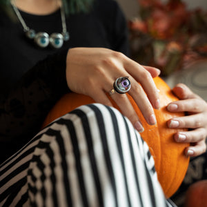 purple ring being worn by model in autumnal theme, model is holding a pumpkin and wearing black and white striped trousers
