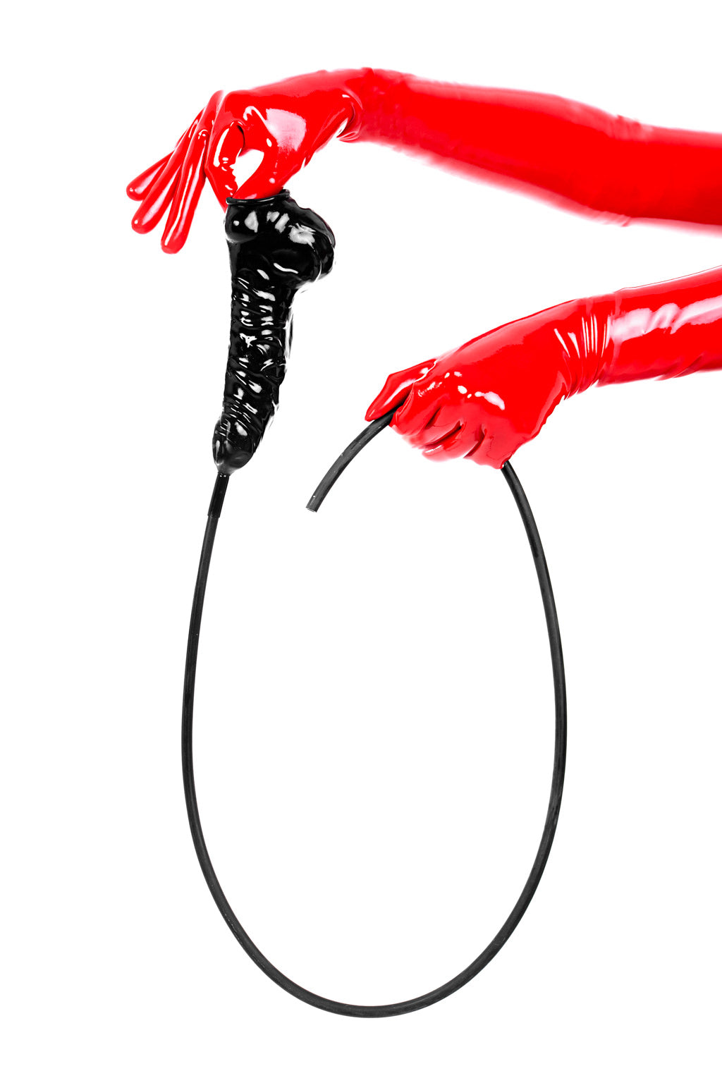 Red latex gloves holding an anatomical cock and ball penis sheath with long flush tube.