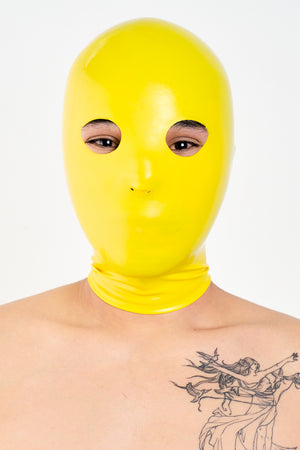 A person wearing a yellow anatomical latex mask.