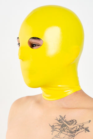 A person wearing a yellow latex anatomical mask.