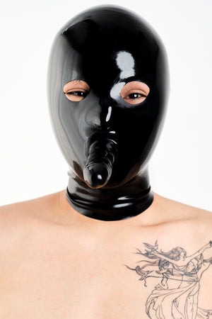 A person wearing a black anatomical latex mask with a dildo.
