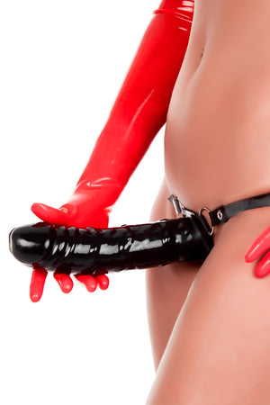A woman wearing a large strap-on dildo.