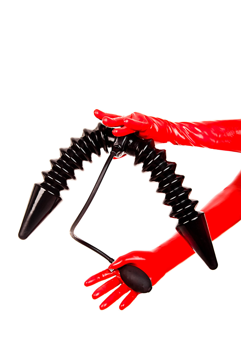 Red latex gloves holding a dual inflatable butt plug with a single pump.